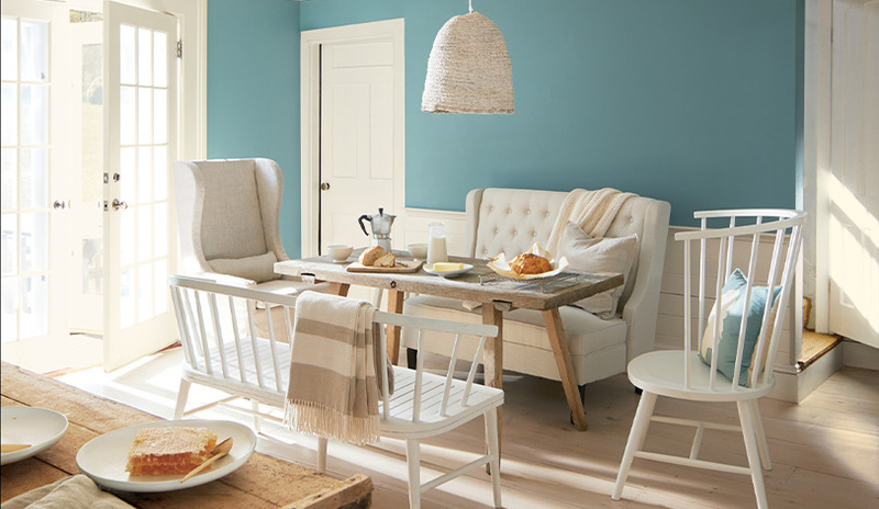 A well-lit dining room area with walls painted in Aegean Teal 2136-40.