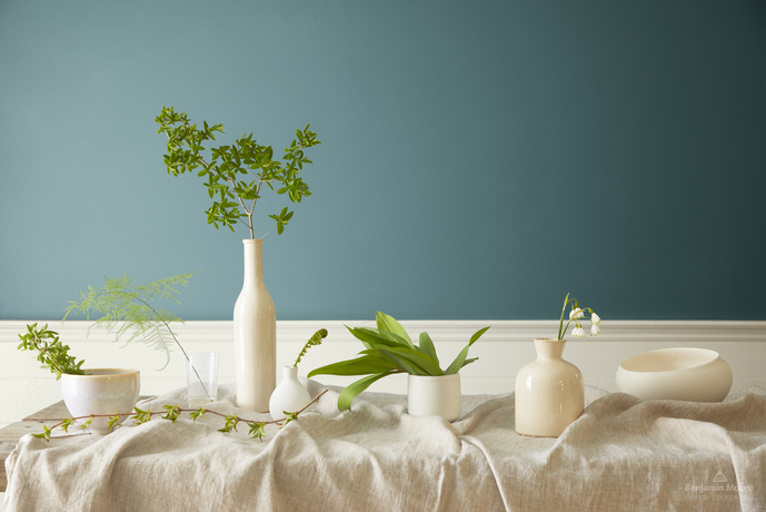 White vases and greenery on a table in front of a wall in Aegean Teal 2136-40.