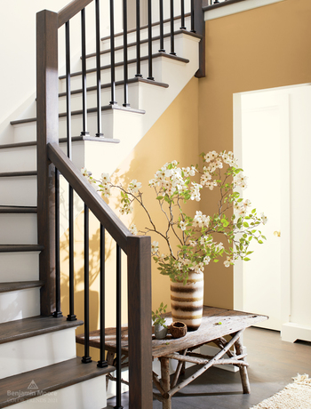 A staircase with wooden railings, white risers, and walls painted in Chestertown Buff HC-9.
